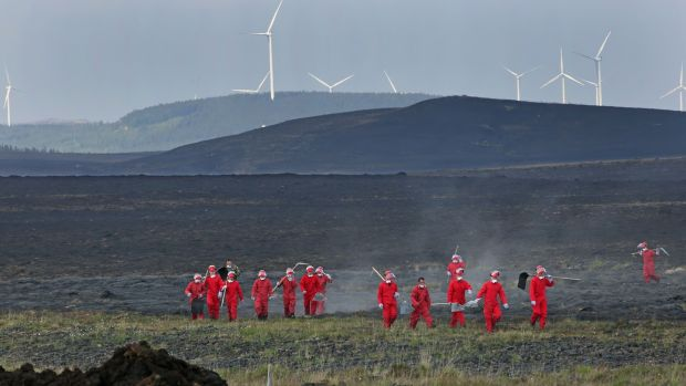 The scorched land with the wind turbines at Cloosh Valley behind as members of the Defence Forces make their way across bogland after extinguishing gorse fires near Inverin in Connemara on Wednesday. Photograph: Joe O'Shaughnessy