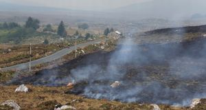 A  cyclist passes by smouldering gorse close to Cloosh Valley in Co Galway. Photograph: Joe O'Shaughnessy