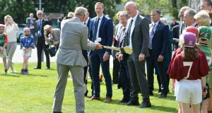 Prince Charles has a hurl as Henry Shefflin and Brian Cody look on during his and the Duchess of Cornwall's visit to Kilkenny Castle. Photograph: Dara Mac Dónaill/The Irish Times