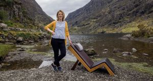 Furniture designer Tricia Harris with her chair the Lazy Lounger  in The Gap of Dunloe, Killarney. Photograph: Don MacMonagle
