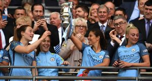 Megan Campbell (left) looks on as her Manchester City team-mate  Carli Lloyd  celebrates with the Women's FA Cup final trophy after the win over Birmingham City at Wembley. Photograph:  Ross Kinnaird/Getty Images