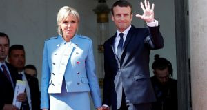 French President Emmanuel Macron and his wife Brigitte Trogneux wave to French President Francois Hollande  as he leaves after the handover ceremony at the Elysee Palace in Paris, France. Photograph: Christian Hartmann/Reuters