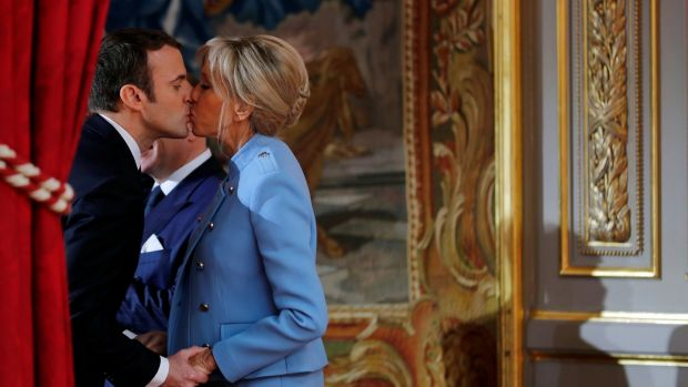 French president Emmanuel Macron kisses his wife Brigitte Trogneux during the handover ceremony in Paris on Sunday. Photograph: Philippe Wojazer/Reuters
