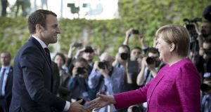 French president Emmanuel Macron is greeted by German chancellor Angela Merkel   upon his arrival at the chancellery in Berlin on Monday. Photograph: Axel Schmidt/Getty Images