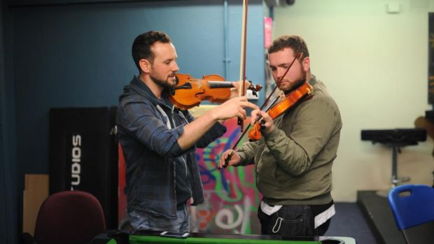 Eoghan Cleary (left) teaches Daniel O'Connor the violin in the music group in The Swan Youth Services in Ballybough, Dublin. Photograph: Aidan Crawley
