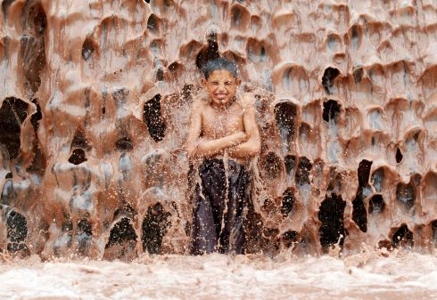 WARM ORDER: An Afghan boy cools off under a muddy waterfall on the outskirts of Jalalabad province, Afghanistan. Photograph: Reuters