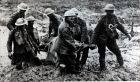 British stretcher bearers carry a wounded soldier in the clinging mud of Passchendaele. Photograph: Paul Popper/Popperfoto/Getty Images