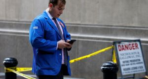 A trader uses his phone outside the New York Stock Exchange  in New York. Photograph: Reuters/Brendan McDermid