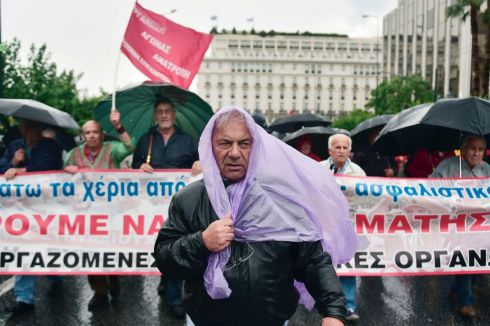 GREEK AUSTERITY: Pensioners march under heavy rain towards the parliament in Athens in protest against fresh pension cuts. Photograph: Getty Images