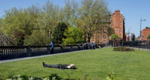 Lazing in the sunshine at St Patrick's Park, Dublin. Photograph: Brenda Fitzsimons / The Irish Times