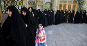 Iranian women queue to vote in the presidential  election – between President Hassan Rouhani and hardliner Ebrahim Raisi – in the city of Qom, south of the capital Tehran, Iran. Photograph: Ebrahim Noroozi/AP
