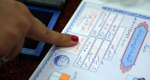 An Iranian woman authenticates a document with her thumbprint ahead of voting for presidential and municipal elections on Friday at the Iranian embassy in Kuwait City. Photograph: Yasser Al-Zayyat/AFP/Getty Images