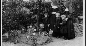 Two nuns and three young girls at the grave of Maj  William Redmond in Locre, Belgium, during the first World War. Redmond was mortally wounded during the Battle of Messines. Photograph:: John Warwick Brooke/National Library of Scotland
