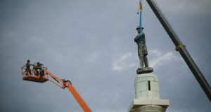 A statue of Robert E Lee is removed from  a 70ft column at a prominent traffic circle in New Orleans, May 19th, 2017. Opposition to the removal of the statue and three others symbolic of the Confederacy has been intense; the state legislature passed a law in an attempt to thwart the removals, and contractors involved have been threatened. Photograph: Edmund D Fountain/New York Times