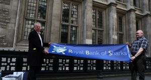 Protestors hold a banner outside of the Royal Courts of Justice as RBS pursued last-minute settlement talks with a group of investors to a trial over allegations the lender misled them about a 2008 capital increase. Photograph: Neil Hall/Reuters