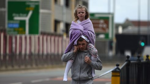 A man carries a young girl on his shoulders near Victoria station in Manchester. Photograph: Oli Scarffoli/AFP SCARFF/AFP/Getty Images