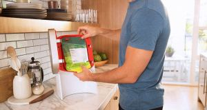 A man uses a Juicero machine - a Bloomberg report discovered users can use their hands to accomplish the task just as well as the $400 device.