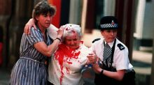 An injured woman is helped away from the scene in Manchester following an IRA bomb blast in June 1996. File photograph: Malcolm Croft/PA
