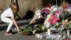 A girl leaves flowers for the victims  in central Manchester. Photograph: Peter Nicholls/Reuters