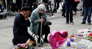 A Jewish woman named Renee Rachel Black and a Muslim man named Sadiq Patel at floral tributes in Albert Square in Manchester. Photograph: Darren Staples/Reuters