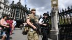 An armed soldier and an armed police officer patrol outside the Houses of Parliament on May 24th, 2017 in London. Photograph:  Carl Court/Getty Images
