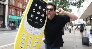 """Yeah, it's rubbish!"": Comedian Dom Joly reunites with a Nokia 3310 on London's Oxford Street. Photograph: Victoria Jones/PA Wire"