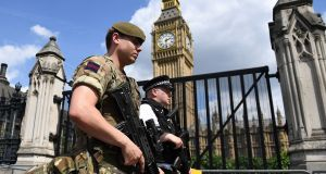 A British army soldier patrols with an armed police officer near the Houses of Parliament in central London. Photograph: Getty Images