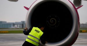 A Wizz Air worker checks an engine of an Airbus 321 in Warsaw. Photograph:  REUTERS/Kacper Pempel
