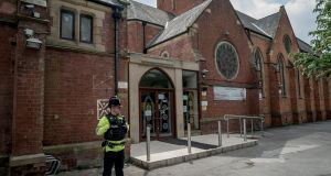 Police stand guard outside the Didsbury Mosque where  Salman Abedi, the bomber responsible for  Monday's attack, had prayed.  Photograph: Andrew Testa The New York Times