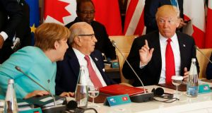 US president Donald Trump talks to German chancellor Angela Merkel and Tunisia's president Beji Caid Essebsi  at the G7 Summit expanded session in Taormina, Sicily, Italy. Photograph: REUTERS/Jonathan Ernst