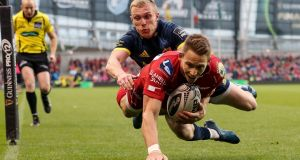 Scarlets' Liam Williams scores the first try of the game despite the tackle of Munster's  Keith Earls. Photograph: Billy Stickland/Inpho