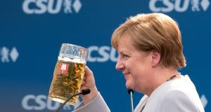 German chancellor Angela Merkel raises a glass of beer after delivering a speech during a joint campaigning event of the Christian Democratic Union (CDU) and the Christion Social Union (CSU) in Munich on Sunday. Photograph: Sven Hoppe/AFP/Getty Images