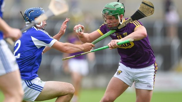 Wexford's Ciaran Lyng with Lee Cleere of Laois during the Leinster senior hurling championship quarter-final at O'Moore Park, Portlaoise. Photograph: Tommy Grealy/Inpho