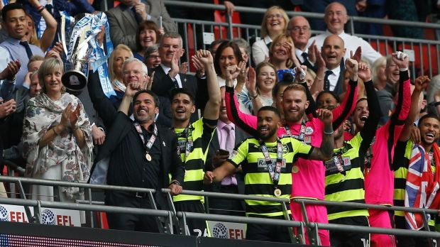 Huddersfield Town manager David Wagner and players celebrate with the trophy. Photograph: Reuters