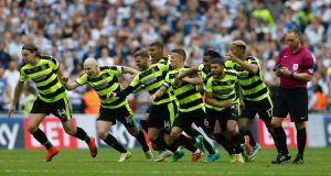 Huddersfield Town players react to the winning penalty at Wembley. Photograph: Reuters