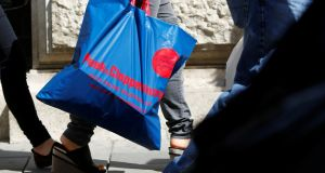 A women carries a shopping bag of German clothing store Peek & Cloppenburg. Photograph: Leonhard Foeger/Reuters