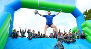 Irish International Rugby star and former Dublin GAA player Kim Flood  with the 1st class students from Scoil Chaitríona, Baggot Street, help  launch Ireland's largest inflatable 5k event, the Wild Air Run.   Photograph: Marc O'Sullivan