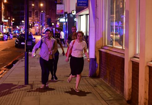 People run down Borough High Street near London Bridge tonight.