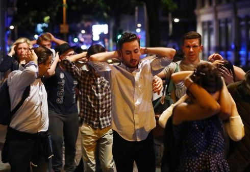 People leave the area with their hands up after an incident near London Bridge. Photograph: Neil Hall/Reuters