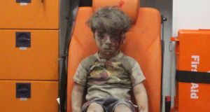 Omran Daqneesh sits inside an ambulance after he was rescued following an air strike in the rebel-held al-Qaterji neighbourhood of Aleppo, Syria, on  August 17th, 2016. Photograph: Mahmoud Rslan/Reuters