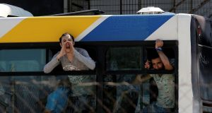 A migrant shouts to journalists from a bus window during a police operation to clear out a makeshift migrant camp at the disused Hellenikon airport in Athens, Greece, in recent days. File photograph: Costas Baltas/Reuters