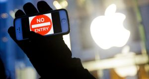 "February 2016:  a man holds up an iPhone displaying a ""No Entry"" image as part of a rally in front of an Apple store in New York in support of the company's privacy policy. Photograph: Justin Lane/EPA"