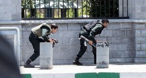 Members of Iranian forces take cover during an attack on the Iranian parliament in central Tehran, Iran. Photograph: Tasnim News Agency/Handout/Reuters