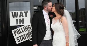 Alliance Party candidate for Belfast West Sorcha Eastwood – with her husband, Dale Shirlow –  at a polling station in Lisburn on their wedding day. Photograph: Brian Lawless/PA