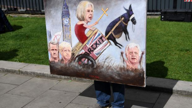 Political artist Kaya Mar holds a painting depicting the faces of British prime minister Theresa May, foreign secretary Boris Johnson, Britain's secretary of state for exiting the European Union David Davis and international trade secretary Liam Fox, as he stands on College Green, opposite the Houses of Parliament. Photograph: Getty Images