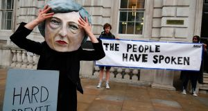 A demonstrator wears a mask depicting British prime minister Theresa May. Photograph: Getty Images