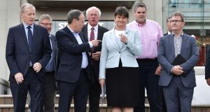 DUP deputy leader Nigel Dodds and party leader Arlene Foster point at each other during a photocall with their newly elected MPs.  Photograph: Charles McQuillan/Getty Images