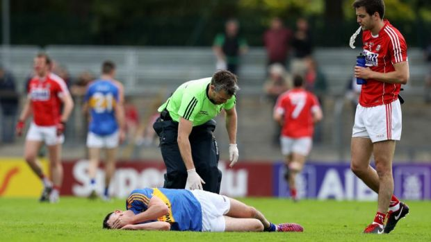 Tipperary''s Michael Quinlivan receives attention after picking up the ankle injury that ended his involvement. Photograph: Tommy Dickson/Inpho