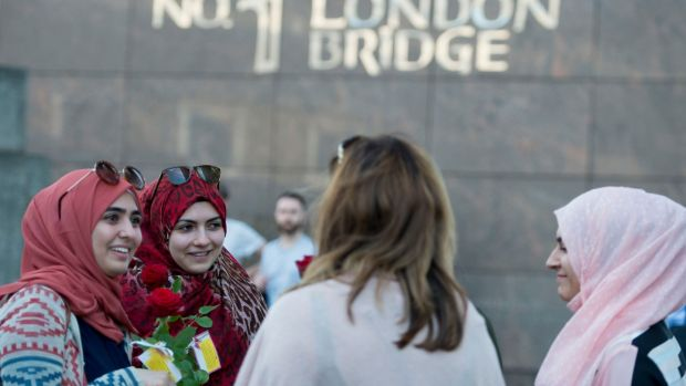 Roses with messages are given out to passers-by on London Bridge.