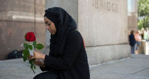 "A woman prepares to give out roses on London Bridge with messages of ""love and solidarity"". Photograph: David Mirzoeff/PA"